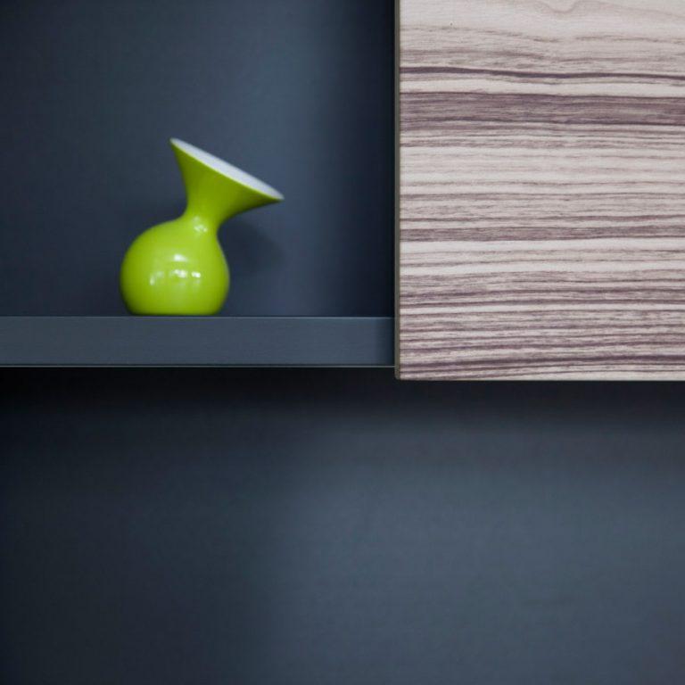 Schwarzes Regal im Wohnzimmer mit grüner Vase und gemaserter Front.